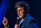Comedian with short hair and glasses holding mic and gesturing with hand.