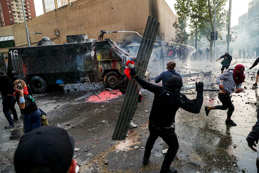A chaotic street scene shows a paint-splattered military vehicle spraying water to ward off hooded protesters.