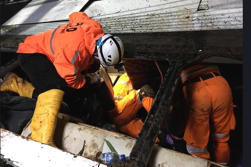 Rescuers search for survivors and victims inside the wreckage of a bus