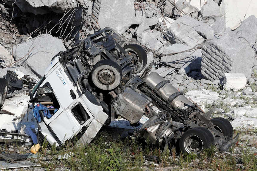 A crushed truck is surrounded in rubble and concrete.