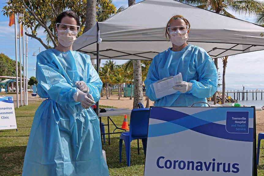 Two nurses wearing protective gear and masks stand in front of a tent on Townsville's foreshore, the beach is in the background