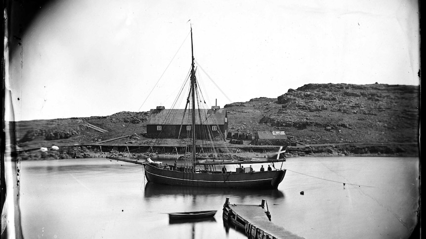 Wide black and white archive shot of a wooden ship moored in a harbour.