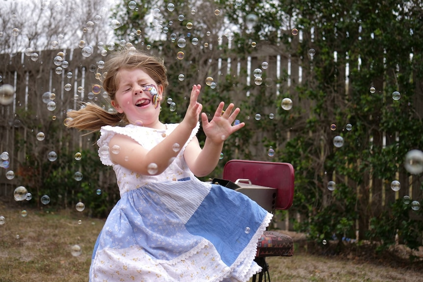 A young girl wearing a blue and white dress, with brunette hair and a unicorn painted on her cheek, running through bubbles.
