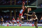 An AFL player leaps high to grab the ball while a defender watches.