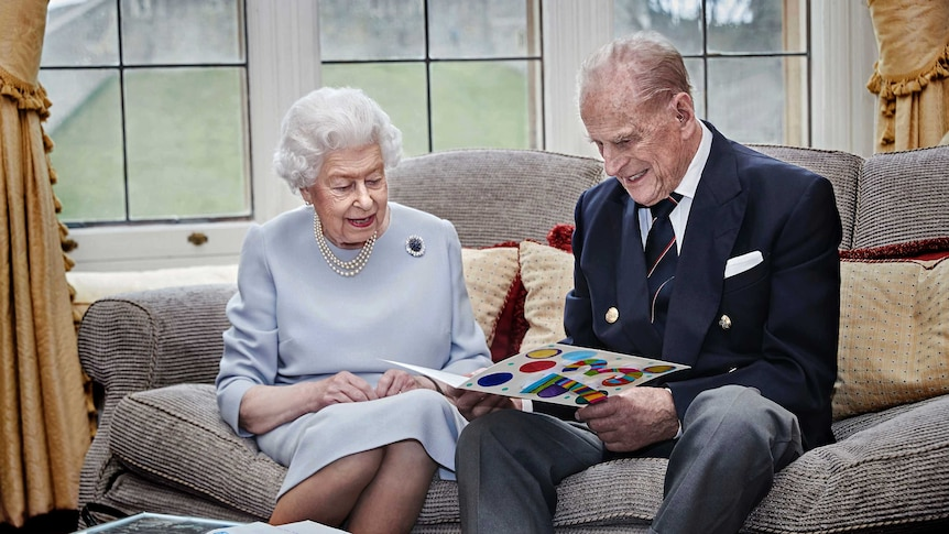 Queen Elizabeth II and Prince Philip smile as they read an anniversary card on a sofa