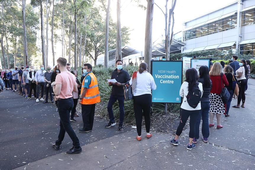 A long outdoor queue with marshals in orange vests