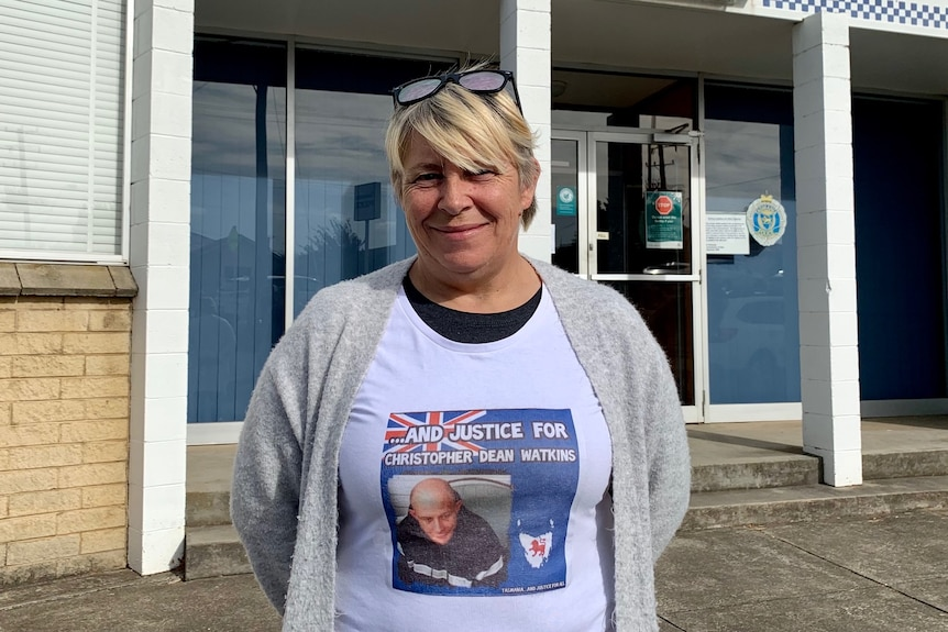 A woman stands outside a police station wearing a shirt with a picture of her missing son on it. He's suspected murdered