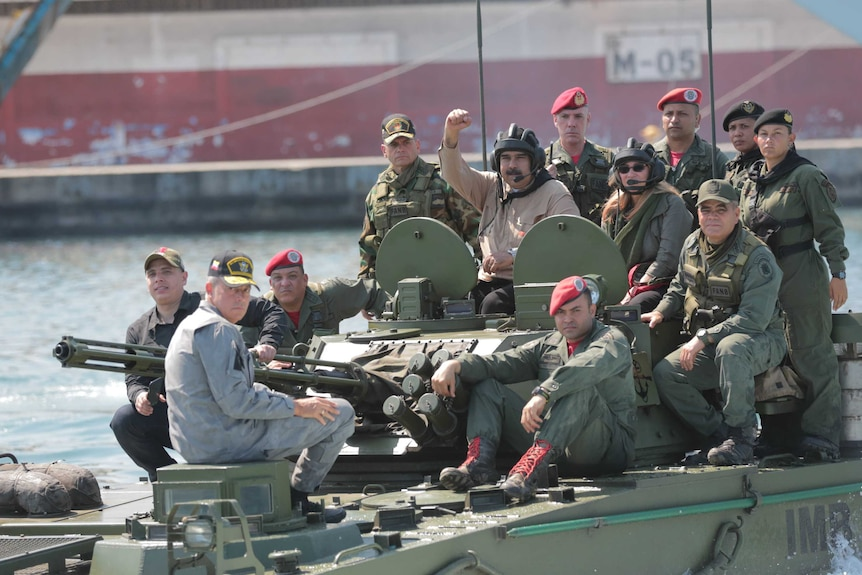 A group of twelve people in military fatigues sit atop a tank with the central figure holding his fist in the air