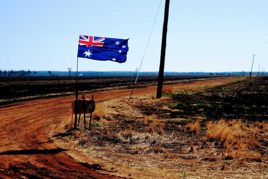 An Australian flag flutters in the wind in a dry landscape in country Australia.