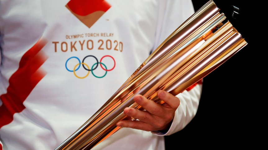 A person in a white t-shirt bearing the Tokyo Olympics logo holding the golden Olympic torch