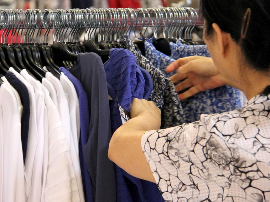 A shopper inspects a garment in a department store.