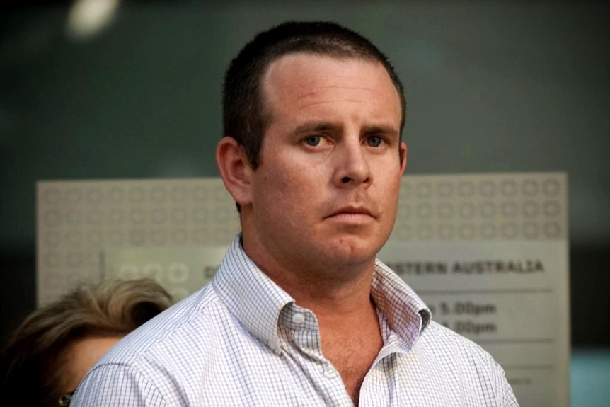 A close up photo of a man with short-cropped hair wearing an open shirt standing outside a court.