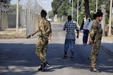 Soldiers are seen patrolling outside fences of the IsoladiCapoRizzutomigrant centre.