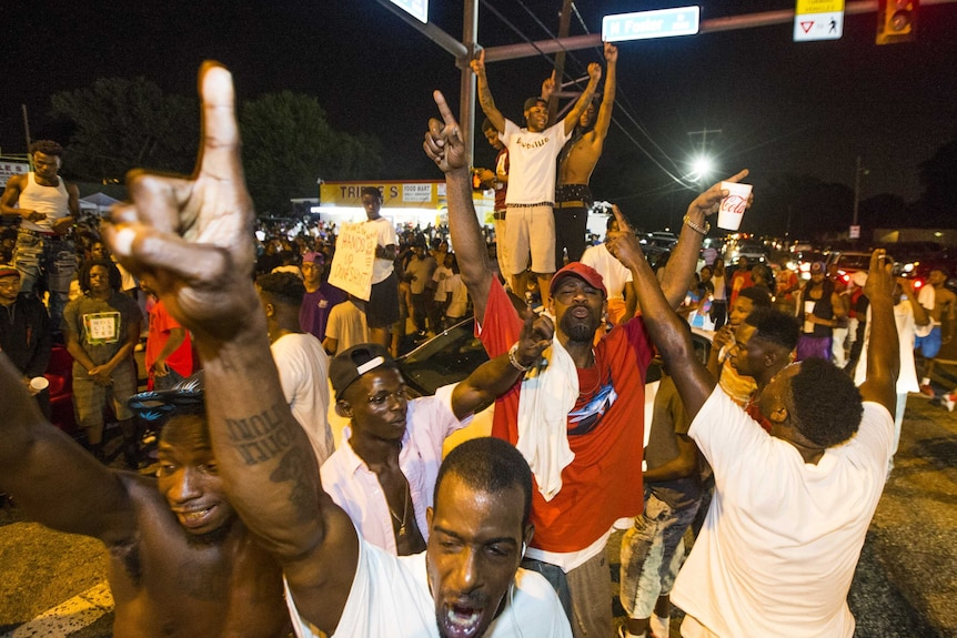 Protesters on the road, blocking an intersection.