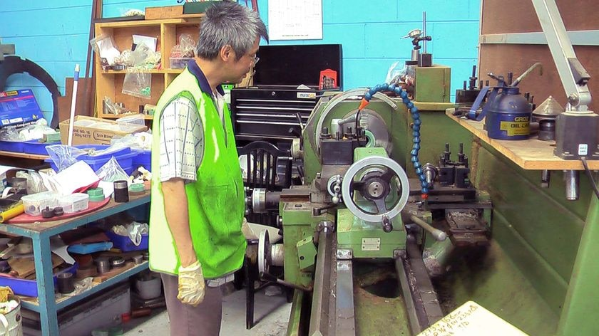 An employee at Associated Gaskets works a lathe at the company workshop