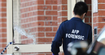 "An AFP officer, with his back to the camera, outside the door of a brick building. His uniform says ""AFP FORENSIC""."