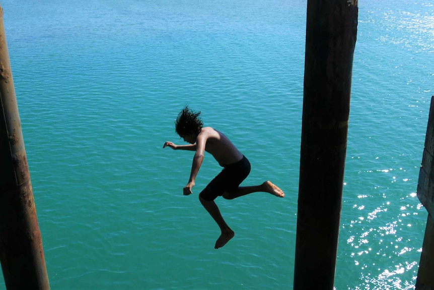 A boy jumps into the ocean off the Palm Island jetty