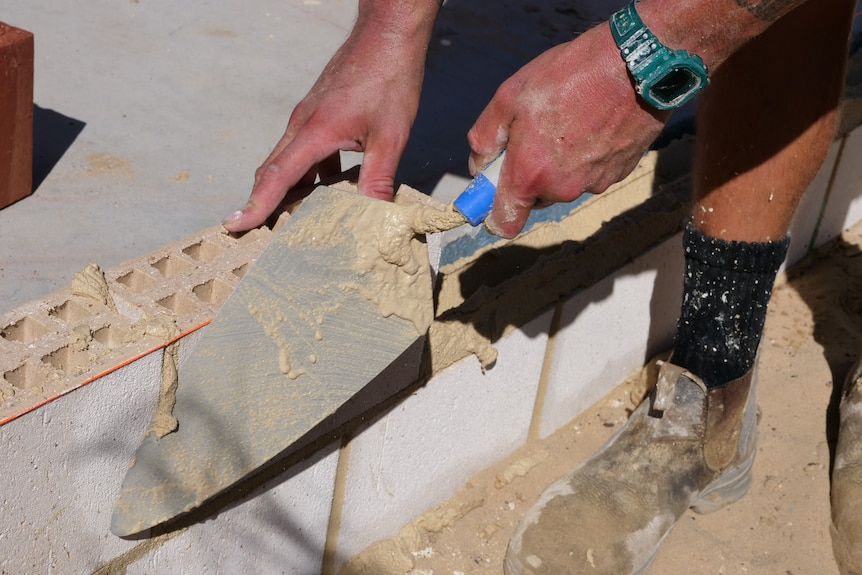 A close up of a bricklayer.
