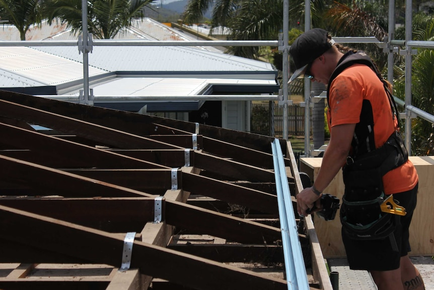 Carpentry apprentice Emily Bailey uses a power drill to work on a roofing project, high up on scaffolding.