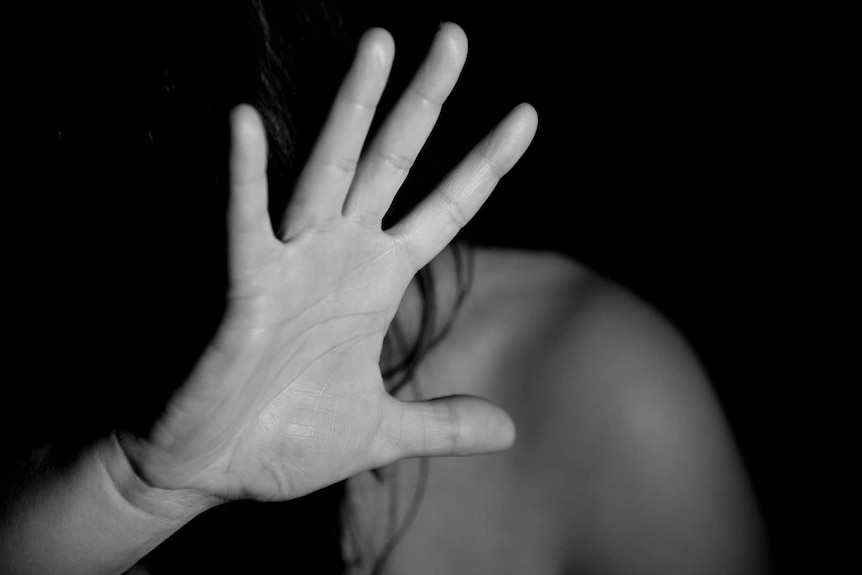 A black and white photo of an unseen woman holding up a hand to protect herself.