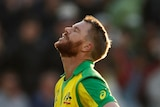 David Warner, with bat and helmet in his hands, closes his eyes and looks to the sky.