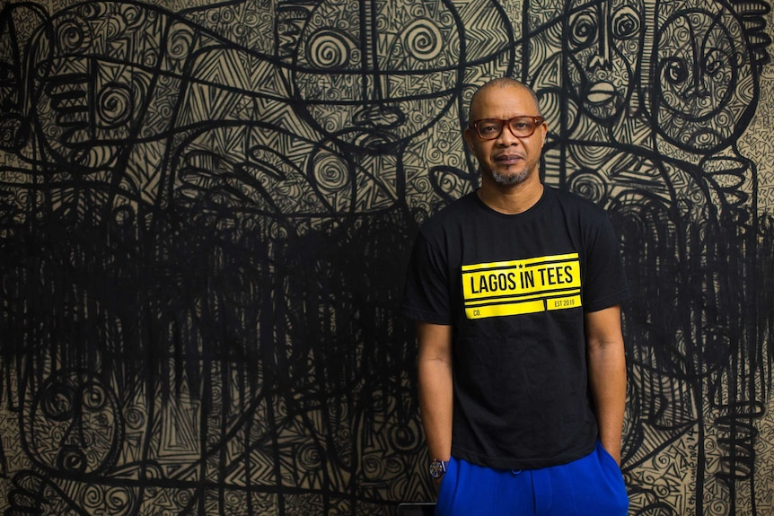 Victor stands in front of a large artwork of figures with complicated patterns drawn in black on a white background.