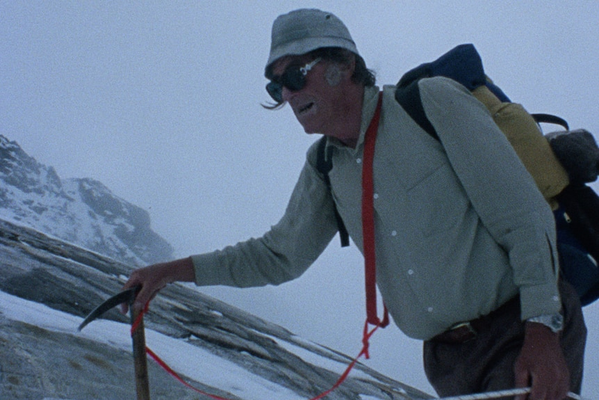 Sir Edmund Hillary with a backpack and ice pick mountain climbing.