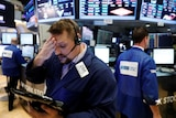 A Wall Street trader holds his head