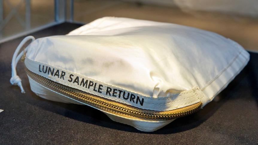 A white, zippered fabric bag with 'Lunar Sample Return' written on it sits on a table.