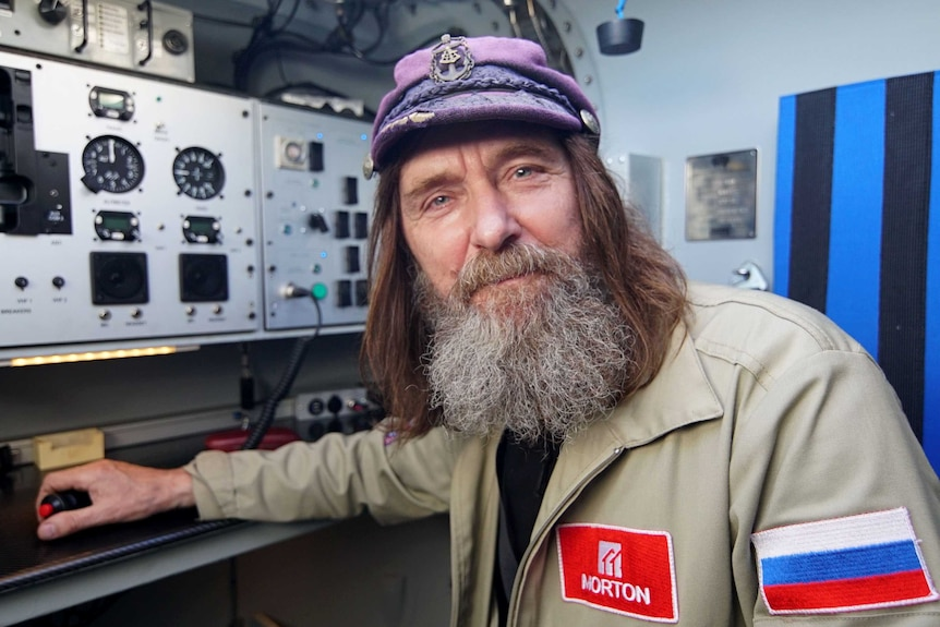 Fedor Konyukhov wearing a sailor-style cap, in the control room of his balloon.