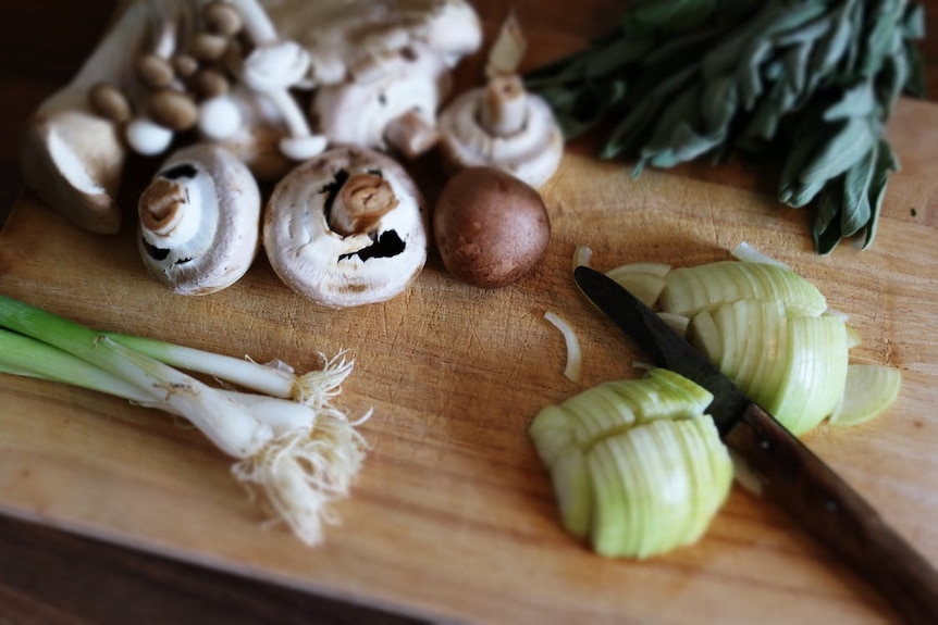Mushrooms and spring onions lie on a wooden chopping board.