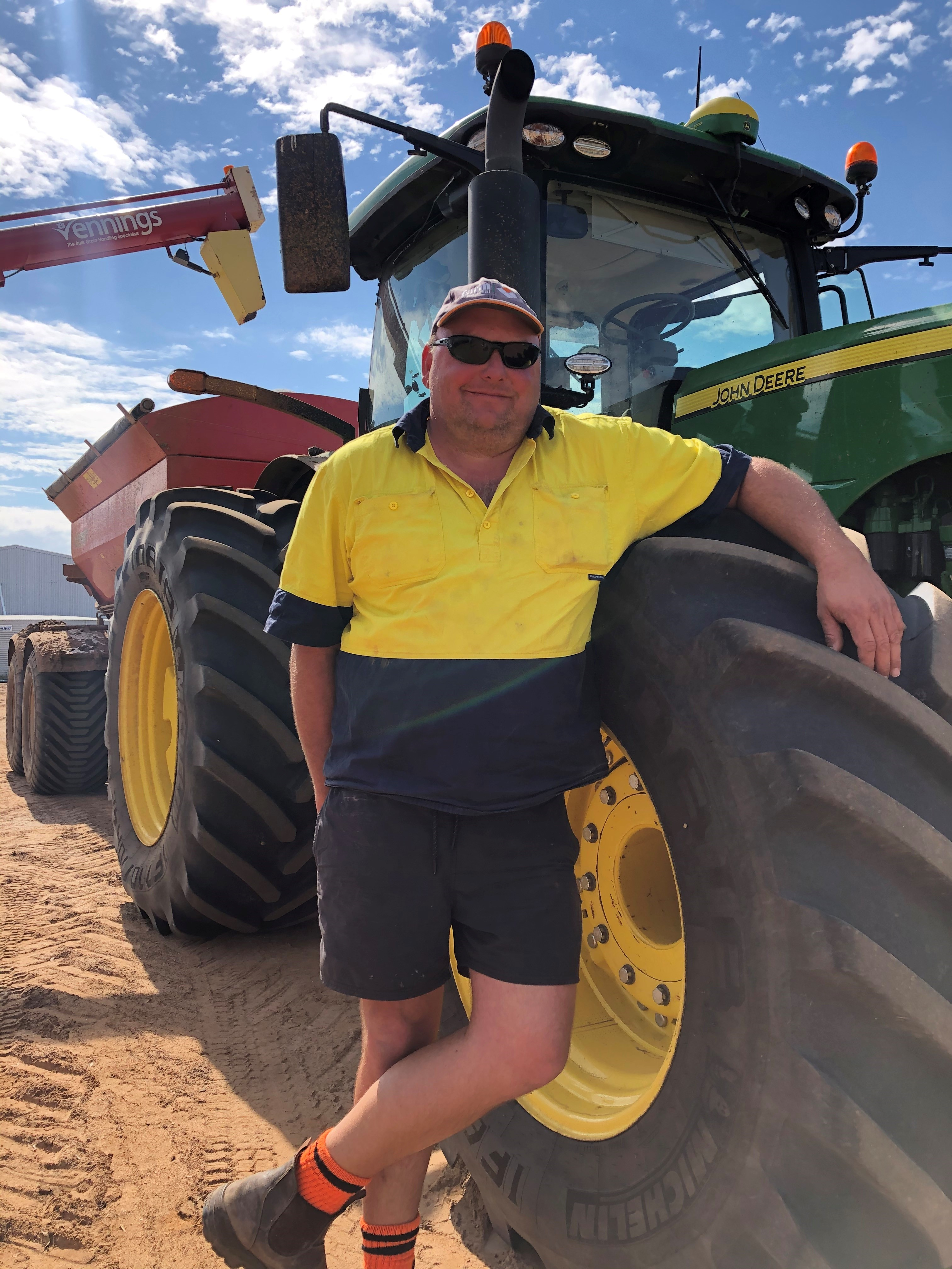 Man in yellow hi-vis shirt and shorts, wearing a light-coloured cap, leans against tractor wheel