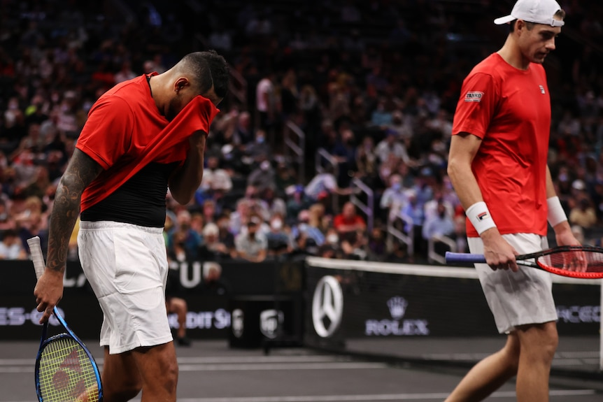 Nick Kyrgios holds his shirt over his face as John Isner looks downwards beside him