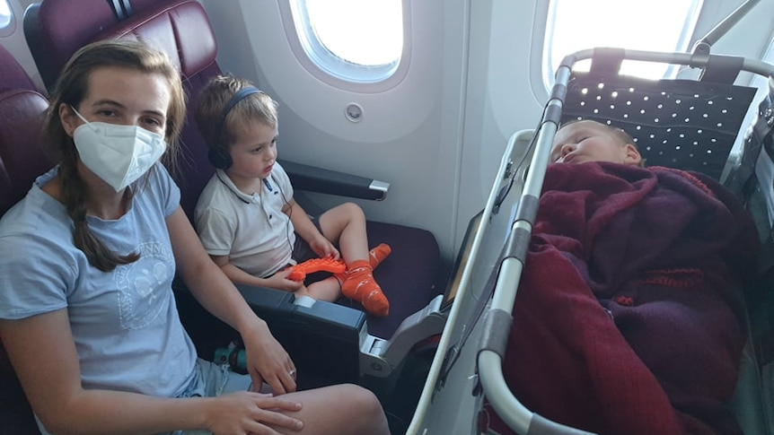 A woman with a mask on sitting on a plane next to a young boy with headphones with a baby sleeping in a travel bassinet infront