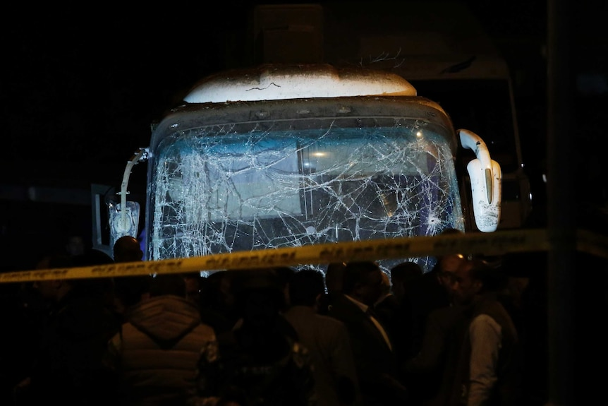Lights are shone on the front of a tourist bus with a shattered windscreen and damaged mirrors.