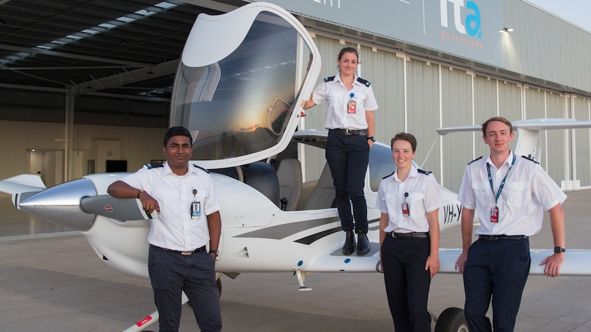 Four students in pilot uniforms stand on or next to a small single engine plane, next to a hangar.
