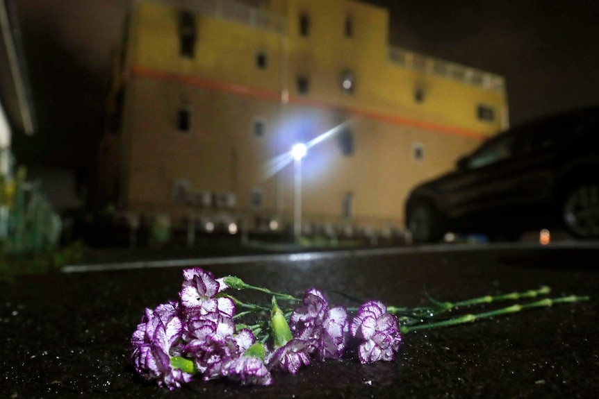 Purple flowers are laid at night following a fire in front of Kyoto Animation building in Kyoto