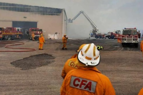 Smoke fills the air around a damaged hay shed as fire fighters look on.