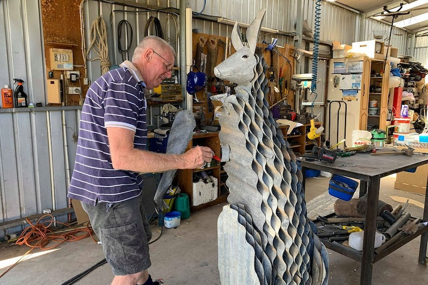 A man is drawing on a metal sculpture of a kangaroo he is making.
