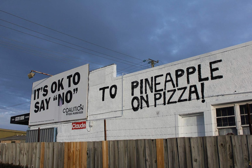 A handpainted message next to a billboard on a pizza shop wall.