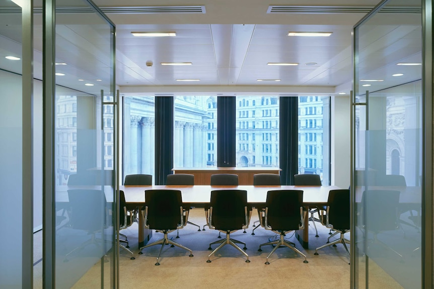 An empty boardroom with chairs around a table