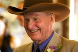 An older man in a cowboy hat and brown formal wear, smiling broadly.
