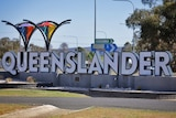 A large white sign of Queensland with individual white letters on concrete blocks in country town.