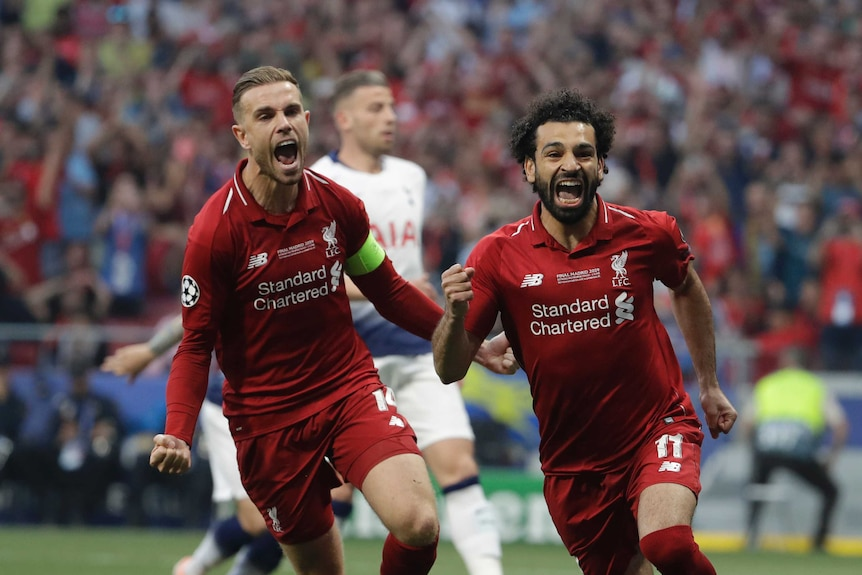 Liverpool's Mohamed Salah, right, celebrates after scoring his side's opening goal