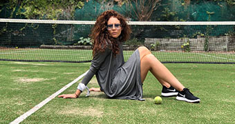 Woman wearing dress and sitting on grass tennis court.