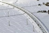 An aerial view of tiny cars in a row topped with snow