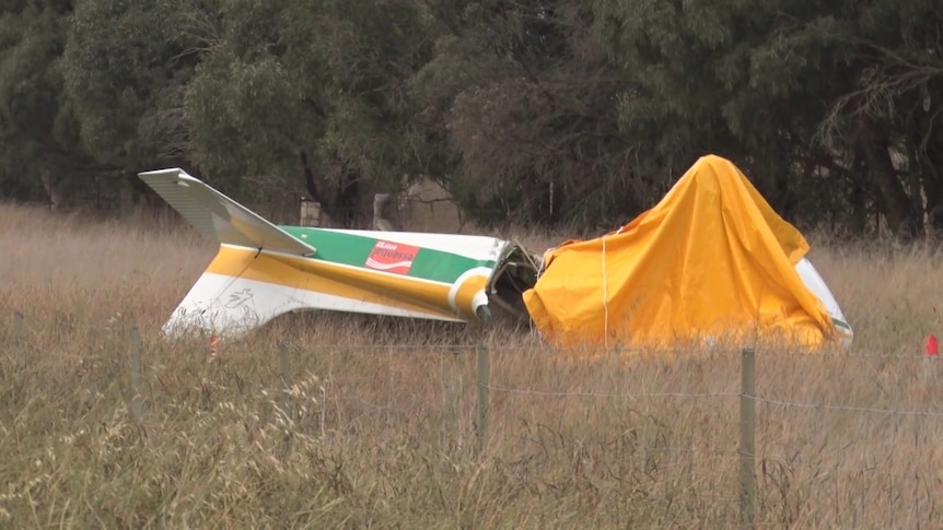 A small aircraft, with a tarp over it, in a field.