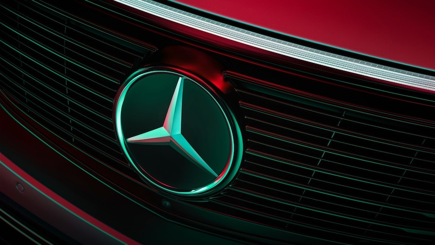 The badge on the front of a red Mercedes-Benz car.