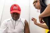 A man of African decent getting the COVID vaccine.