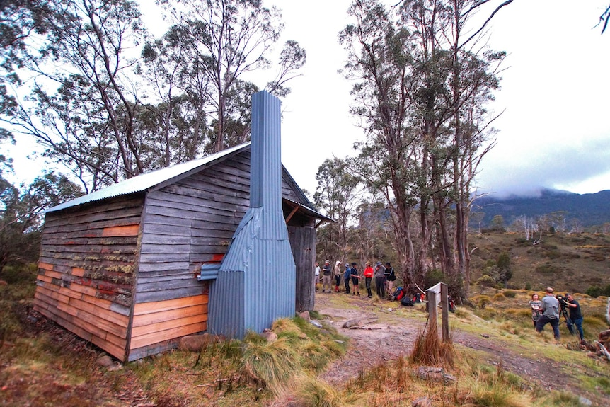 a group of people stand around an old hut in the bush